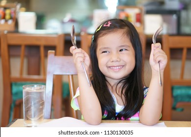 Asian children cute hungry or kid girl holding spoon and fork for wait eat delicious food with smile and happy for lunch or breakfast in morning with drink water at restaurant or home and kitchen room