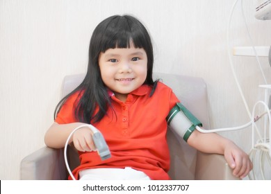 Asian children cute or kid girl happy and smile for health check with pressure gauge and pulse gauge at healthcare hospital with wear red shirt