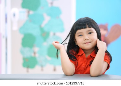 Asian children cute or kid girl happy fun and smile with wear red shirt on sofa at preschool or nursery and child hospital with space