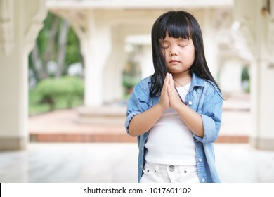 Asian children cute or kid girl pay obeisance and pray close eye with wear white clothes and jean shirt in the pavilion garden at church or temple for peace with space