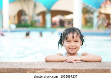 Asian children cute or kid girl swimming and smile with happy fun on swimming pool or water park for refreshing and relax with exercise at summer holiday