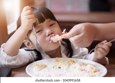 Asian children cute or kid girl eating shrimp or shrimp fried rice delicious food with mother or father feed baby on white dish for lunch or breakfast in morning with sunlight at restaurant or home