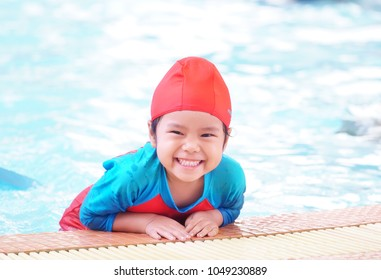 Asian children cute or kid girl wear swimming suit on swimming pool and smile with happy fun in water park for learning or refreshing and relax with exercise on summer holiday with space