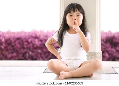 Asian children cute or kid girl squat and forefinger close mouth for tell quietly or stop and secret surprise with play hide and seek at back pole with pink tree and space