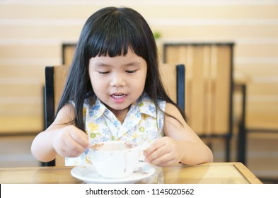 Asian children cute or kid girl smile white teeth and delicious hot cocoa or milk chocolate drink in white cup sloppy with fun and happy for breakfast in morning on table at home or cafe restaurant