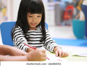 Asian children cute or kid girl smile and learning for coloring or paint on white paper with teacher or mother at nursery or school on soft focus