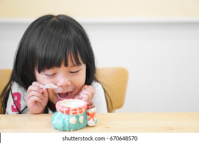 Asian children cute or kid girl scream happy to delicious eat dessert or milk ice cream in colorful ceramic cup on the wood table in restaurant or cafe for background with space and soft focus