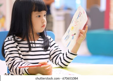 Asian children cute or kid girl learning for coloring or drawing paint on white paper and colorful table with chair at nursery or pre school on soft focus