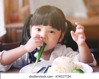 Asian children cute or kid girl eating spring onion or vegetable in shrimp fried rice delicious food on table and white dish for lunch in the restaurant with vintage style