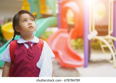 Asian children cute or kid girl student wearing school uniform and back to school for study and education with looking ahead and future or miss something on playground with warm sunlight and vintage
