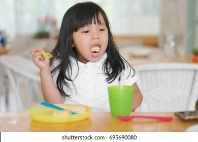 Asian children cute or kid girl enjoy eating dessert and open mouth for eat delicious bread with colorful container or utensil plastic for baby on wood table in cafe restaurant for breakfast and lunch