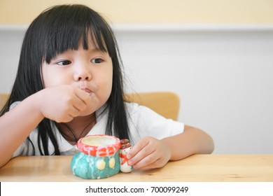 Asian children cute or kid girl happy to delicious eating dessert or milk ice cream in colorful ceramic cup on the wood table in restaurant or cafe for background with space