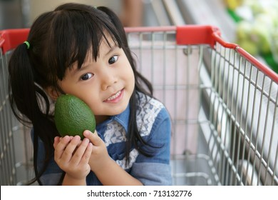 Asian children cute or kid girl smile white teeth with holding avocado fruit and sit on supermarket cart for sell or buy and eat in the super market with space