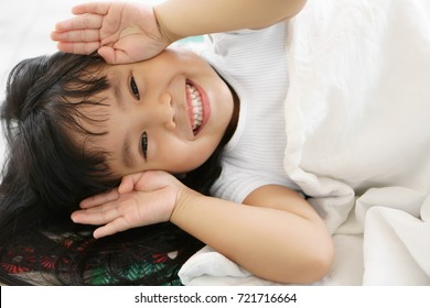 Asian children cute or kid girl sleep with open hand from eye for enjoy playing peekaboo or hide and seek with smile white teeth
