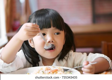 Asian children cute or kid girl enjoy eating shrimp fried rice delicious food on wood table and white dish for breakfast or lunch and dinner in the cafe restaurant with holding spoon and fork