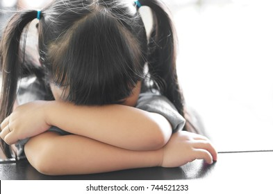 Asian children cute or kid girl sleeping and cry with sad or sick on the black table at nursery or kindergarten and preschool with white space