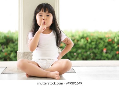 Asian children cute or kid girl squat and forefinger close mouth for tell quietly and secret surprise with play hide and seek at back pole with space