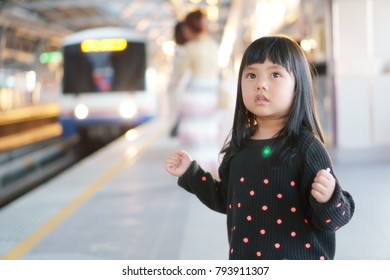Asian children cute or kid girl waiting sky train or electric train on railway station or platform and nature sunlight in the city for travel with space
