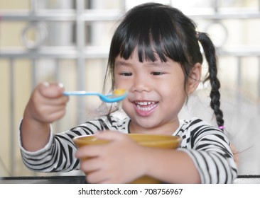 Asian children cute or knit braid kid girl enjoy eating rice porridge or congee food with egg or yolk scoop and smile white teeth for breakfast before go to school in the morning
