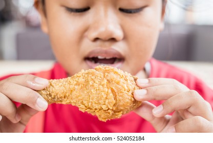 Asian children eating fried chicken in the restaurant. Focus on chicken