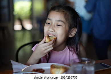 Asian Children are eating Garlic bread