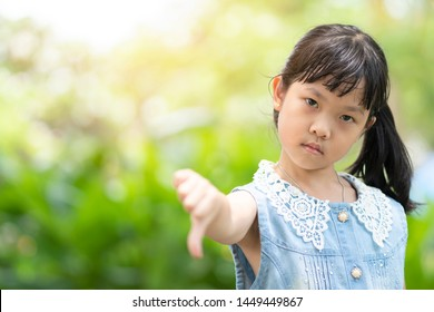 Asian children Face showing a feeling of discontent She turned her thumb down. Show anger