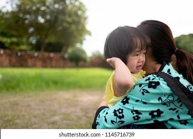 Asian children feel sad to hug mother in the garden.