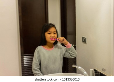 asian children girl Brushing teeth In front of the bathroom