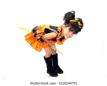 Asian children girl in pumpkin dress costume for Halloween decoration in Riding a broom white background