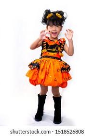 Asian children girl in pumpkin dress costume for Halloween decoration Holding a pumpkin in white background