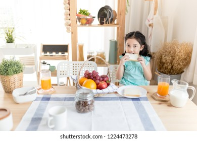 Asian children have a breakfast in the morning, she holding and bite a bread, child nutrition and development, she feeling happy in eating time