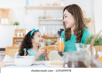 Asian children and her mom drink orange juice in the morning, they holding orange juice glass in kitchen room, child nutrition and development, they feeling happy in family time