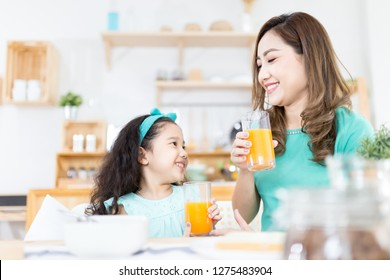 Asian children and her mom drink orange juice in the morning, they holding orange juice glass, child nutrition and development, they feeling happy in family time, health promotion