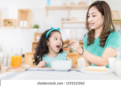 Asian children and her mom have a breakfast in the morning, child nutrition and development, they feeling happy in family time