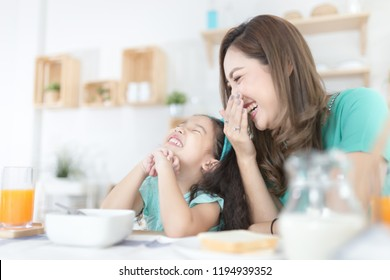 Asian children and her mom have a breakfast in the morning, child nutrition and development, they laughing and feeling happy in family time