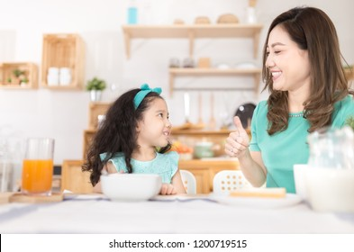 Asian children and her mom have a breakfast in the morning, asian mother feeling glad and show thumbs up sign with her hand, child nutrition and development, they feeling happy in family time