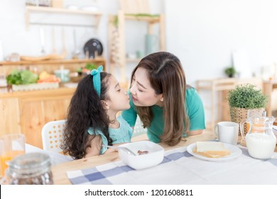 Asian children and her mom have a breakfast in the morning, asian mother feeling glad and kiss her daughter, child nutrition and development, they feeling happy in family time