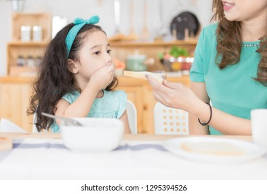 Asian children and her mom have a breakfast in the morning, asian children don't want to eat, she use her hand close her mouth, child nutrition and development, anorexia
