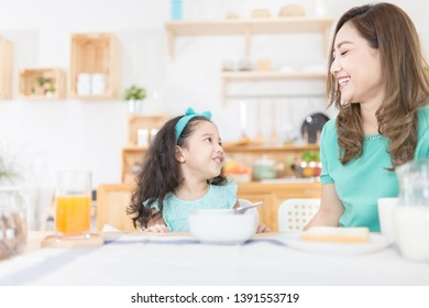 Asian children and her mom have a breakfast in the morning, child nutrition and development, they feeling happy in family time, they talk and smile
