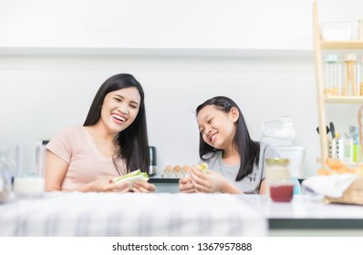 Asian children and her mother have a breakfast in the morning, child nutrition and development, they feeling happy in family time