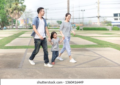 Asian children and her parent relax in public garden, they holding hand and walk in family time, family happiness activity
