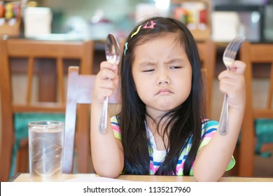 Asian children hungry or kid girl holding spoon with fork and unhappy or angry and touchy frown for long time wait eat delicious food or anorexia and bored food for breakfast in morning at restaurant