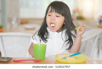 Asian children or kid girl enjoy eating bread dessert and stick in one's throat with choke food or puke with colorful plastic dish and cup for baby on table in restaurant for breakfast or lunch