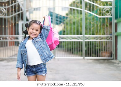 Asian children or kid girl smile and student holding and show pink schoolbag with happy fun because go to school or back to school and kindergarten from summer study or learning to home and wear jeans