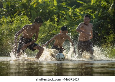 Asian children play soccer in the river, Soccer players in action on the river at sunset.