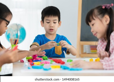 asian children playing clay coloured on the table in the classroom summer back to school concept