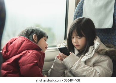 Asian children playing game on mobile together,They travels on a train