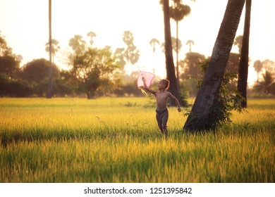 Asian children playing kites in the rice paddy countryside at Suphanburi Province in Thailand.