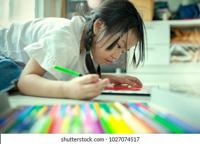 asian children playing and painting color pencil on paper book in home school