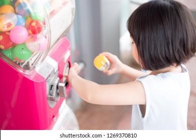 Asian children playing toy vending machine, dispenser toy, Gumball Machine